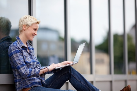 surfing the internet: Pretty blond student using her laptop in the city sitting leaning against a glass storefront while sitting on the sidewalk