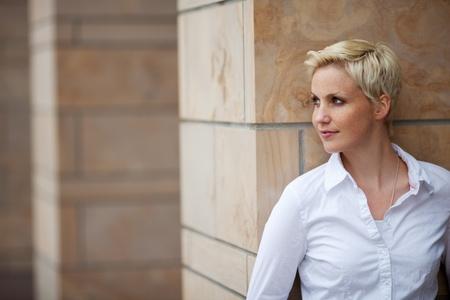 horizontal haircut: Beautiful young woman looking away while leaning on pillar