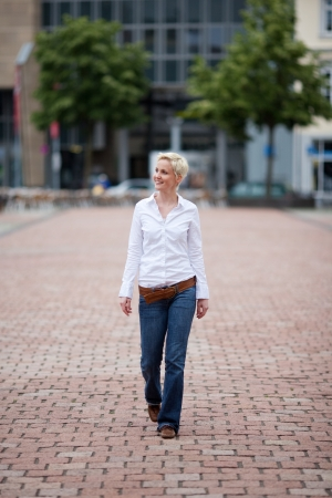 Casual pretty young woman walking down an urban street with brick paving looking off to the left of the frame photo