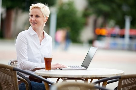 Young woman with a laptop in a outdoor cafe photo