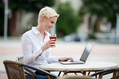 Happy young blond woman using a laptop at an open-air restaurant sitting outdoors at a table on the street holding a cold drink in her hand Stock Photo - 20662486