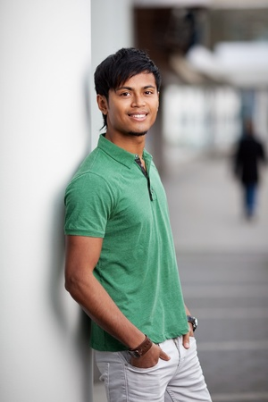 immigrant: Handsome young indian man leaning against wall Stock Photo