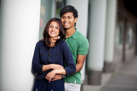 young smiling couple in love standing outdoors photo
