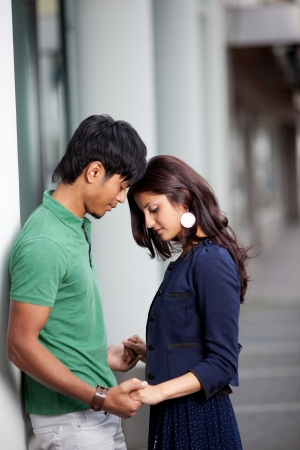 Romantic young Asian couple holding hands and touching foreheads with a loving gesture as they stand outdoors against a row of pillars