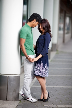 Loving fashionable young Asian couple in town standing close together facing each other and holding hands with their foreheads touching outside an urban building with pillars photo