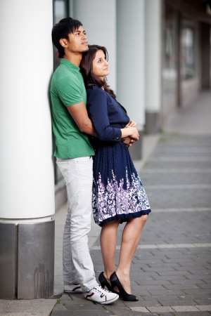 happy asian couple standing in the city