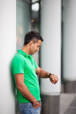 standing against: Young Asian man waiting for something standing leaning against an urban building and looking at the time on his wristwatch