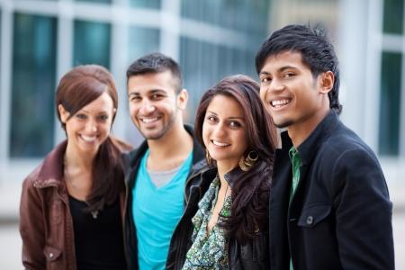 multicultureel: Twee aantrekkelijke jonge Aziatische koppels ontspannen in de stad staan dicht bij elkaar lachend in de camera