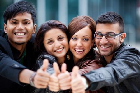 optimismo: Grupo feliz optimista de j�venes amigos asi�ticos de pie con las cabezas muy juntas riendo y dando un pulgar hacia arriba gesto