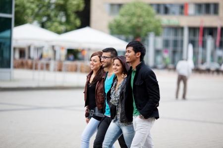 parejas caminando: Cuatro j�venes amigos de moda de Asia caminando por la ciudad, junto a lo largo de una calle urbana