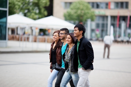 Four fashionable young Asian friends walking through the city together along an urban street Stock Photo