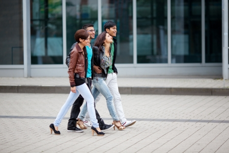 abreast: Four trendy young Asian friends walking arm in arm along the street through town past store windows Stock Photo