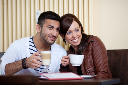 Loving Asian couple in a restaurant sitting with ther heads close together enjoying coffee and macchiato photo