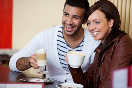 Laughing attractive young Asian couple in a sitting side by side at a table in a restaurant enjoying coffee together photo