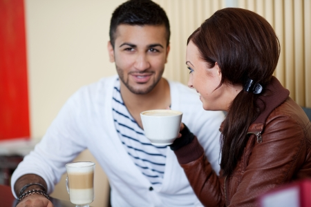 beautiful young couple talking in a cafe photo