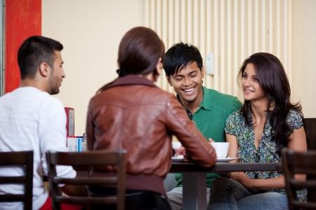 man drinking coffee: Talking in a coffe shop between good friends Stock Photo