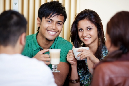 Great looking couple smiling at camera in a cafe photo
