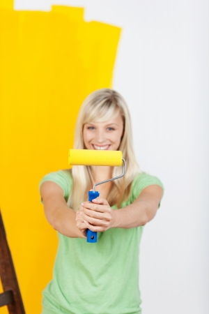 Vivacious woman painting with yellow paint holding up a paint roller in front of her with a pleased satisfied smile Stock Photo - 20679478