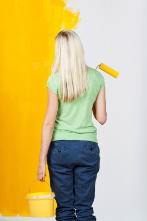 Woman standing with her back to the viewer and a tub of paint and roller in her hand contemplating a half painted wall with one half white and the other yellow in a before and after concept photo