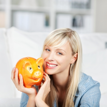 piggybank: Happy beautiful woman holding her cute fat bright yellow piggybank to her cheek with a pleased smile Stock Photo