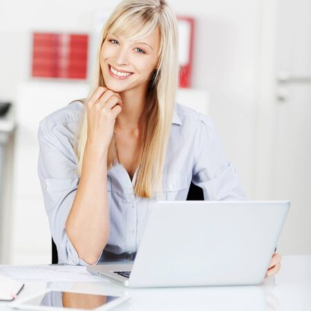 Blond woman browsing the internet using her laptop photo