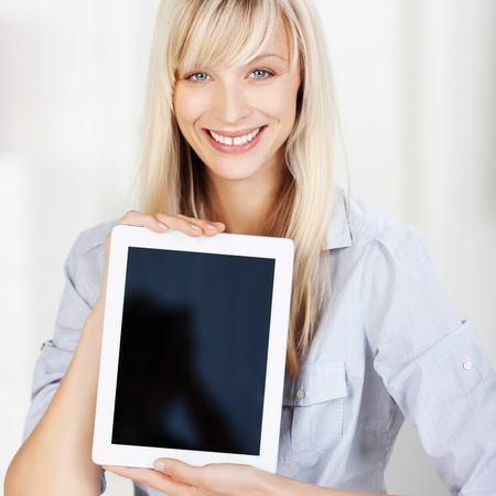 facing: Smiling beautiful young woman holding up a blank tablet with the screen facing the viewer with copyspace for your text Stock Photo