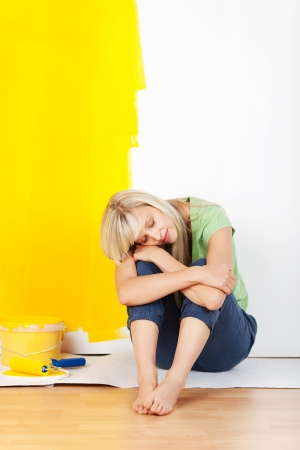 Exhausted woman taking a break from decorating her house and painting the walls sitting on the floor with her head on her arms and a half painted yellow wall behind photo