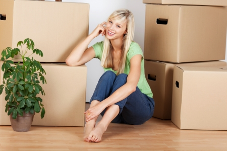 unlabelled: Beautiful young female sitting next to boxes in new house