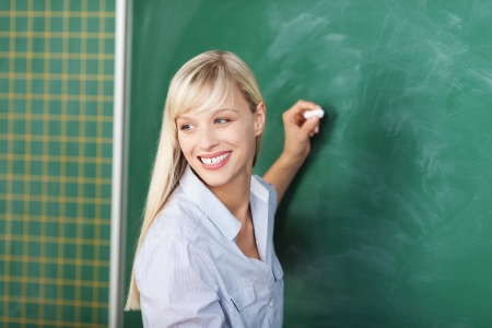 Blond female writing on the green board in a close up shot photo