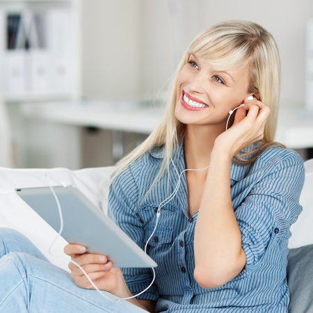 Beautiful blonde woman smiling while listening to music on her tablet as she sits comfortably on a sofa in her living room photo