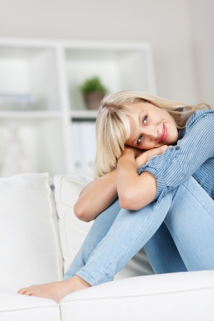 introspective: Young woman sitting and embracing her legs, isolated on a blurred background Stock Photo