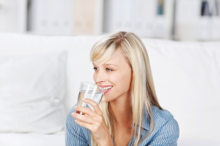 blonde: Smiling healthy woman drinking a large glass of bottled mineral water to quench her thirst