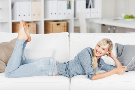 Happy woman listening to music and lying on a white couch with tablet photo