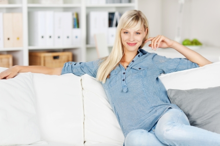 Smiling Caucasian woman sitting and posing on the couch Stock Photo - 20680243