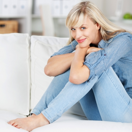 attractive couch: Smiling woman relaxing and embracing her legs