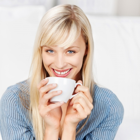 Smiling woman drinking a cup of coffee in a close up shot photo