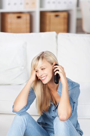 Smiling woman sitting on the floor and calling on her mobile phone photo