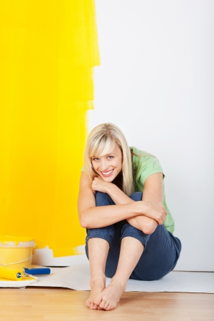 Cheerful woman sitting on the floor after painting a room in her new house photo