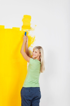 Cheerful blond woman painting wall with roller Stock Photo - 20662816