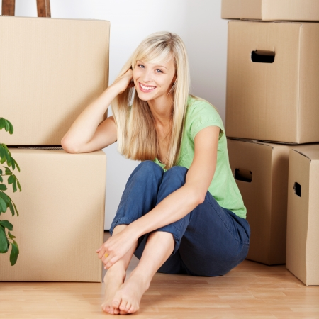 Beautiful smiling young woman sitting barefoot on the floor surrounded by cardboard cartons when packing to move house photo