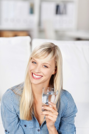 Beautiful woman with a lovely vivacious smile drinking a glass of fresh pure water photo