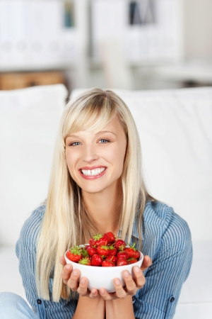 Smiling attractive young blonde woman with a bowl of delicious ripe red strawberries held in her hands photo