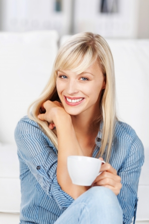 Beautiful long haired blonde woman relaxing on the sofa at home with a cup of coffee giving the viewer a lovely smile photo
