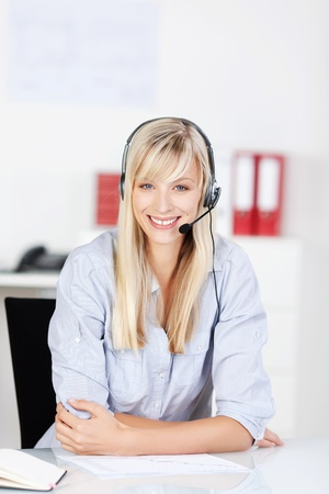 Young blonde call center agent sitting against the blurred background photo