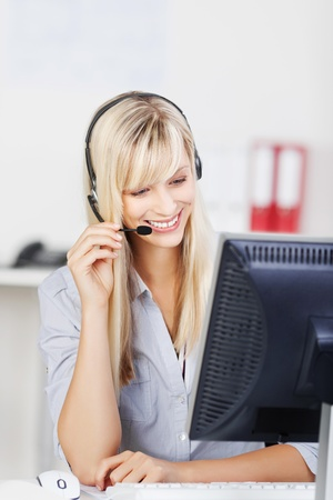 telephonist: Female call center agent smiling while browsing in her computer