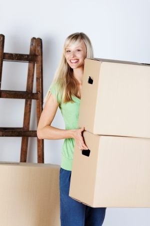 unlabelled: Attractive young blond woman carrying brown cardboard packing cartons as she moves house to new premises Stock Photo