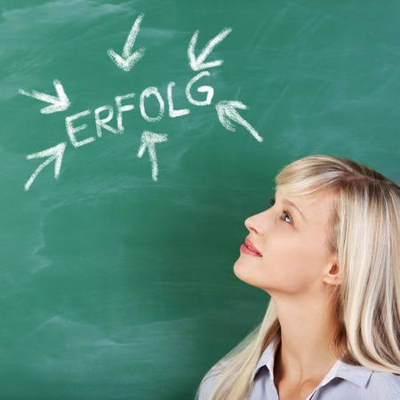 Portrait of woman looking at the green board with an arrow and letters photo