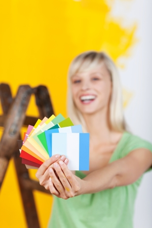 colours tints: Happy woman holding a paint color choices over a yellow paint wall