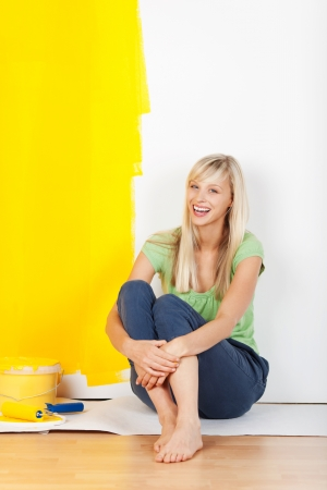 Laughing casual barefoot young woman taking a break from painting sitting on the floor with a half painted yellow and white wall behind her showing the before and after colours photo
