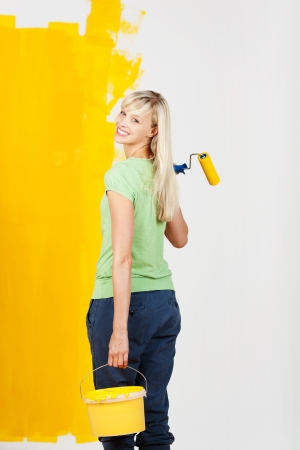 Smiling young woman carrying yellow paint in a container and a roller in her hand turning back to look at the camera as she prepares to continue decorating her house photo